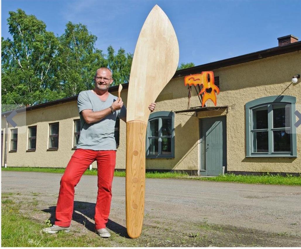 En man står bredvid Världsrekord för den största smörkniven. Träffa denna världsrekordshållare i Uddebo med Meet the Locals.