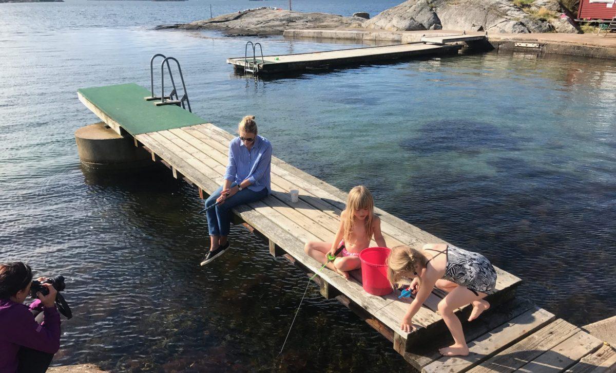 Familj fiskar krabbor på bryggan i Billdal. Fiska krabbor i skärgården med Meet the Locals.